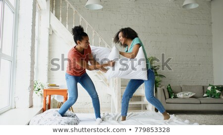 happy female friends having pillow fight at home Stock photo © dolgachov