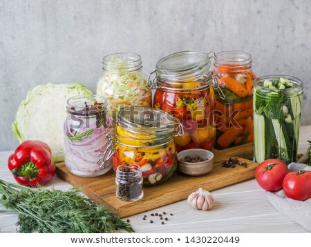 Pickled tomato in jars on wooden table . Tomatoes fermented process glass jars variety - red yellow, Stock photo © Virgin
