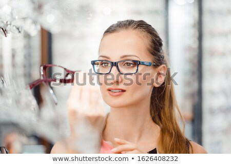 Woman being satisfied with the new eyeglasses she bought in the store Photo stock © Kzenon