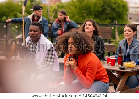 Young hockey fans watching attentively match broadcast Stock photo © pressmaster