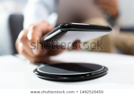 Man Charging Smartphone Using Wireless Charging Pad  Stock photo © AndreyPopov