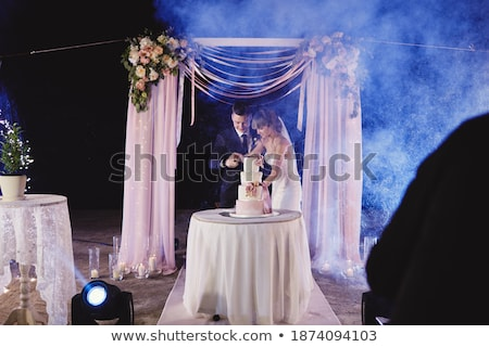 Happy bride and groom cut the cake. Evening ceremony Stock photo © ruslanshramko
