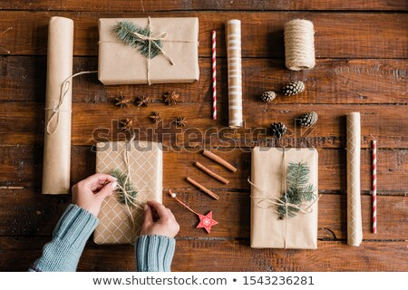 hands of young woman in blue sweater making knot on top of one of giftboxes stock photo © pressmaster