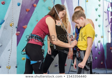 Young female climbing instructor attaching rope to safety belt of youthful boy Stock photo © pressmaster