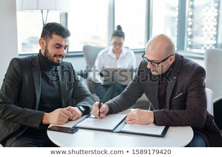 Two successful business partners signing financial documents in hotel lounge Stock photo © pressmaster