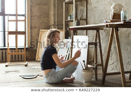 Beautiful young woman artist sitting in the art studio Stock photo © deandrobot