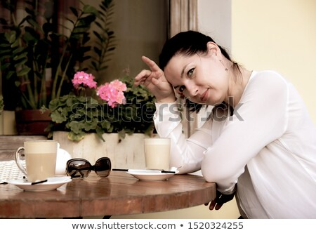 Stock photo: beautiful woman looking at the cappuccino coffee in front of her on the table
