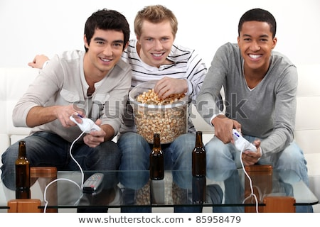 Three friends playing video games while drinking beer. Stock photo © photography33