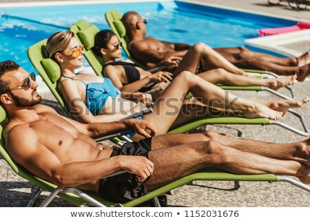 Young couple sunbathing at the poolside Stock photo © photography33