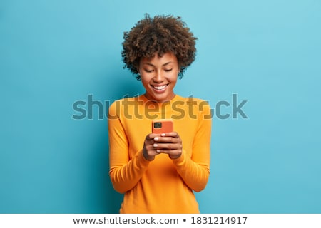 pretty young female sending message by cellphone stock photo © pablocalvog