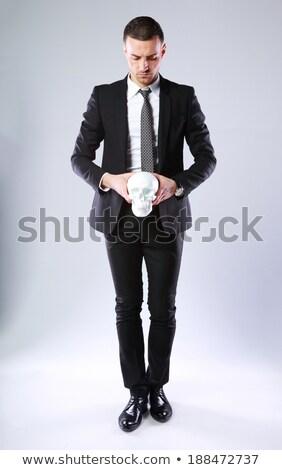 Full-length portrait of a confident businessman holding skull over gray background Stock photo © deandrobot
