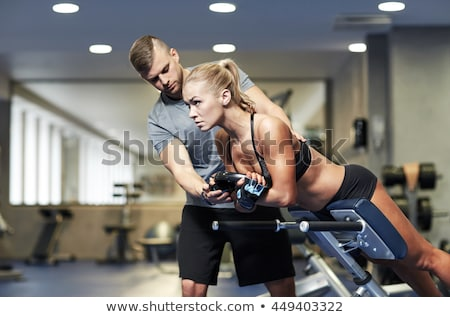 Fit woman flexing back muscles on bench Stock photo © deandrobot