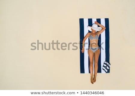 Tomar el sol playa nina toalla de playa sol puesta de sol Foto stock © alphaspirit
