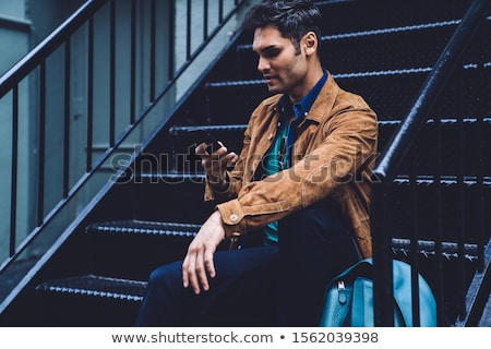 young man ironing clothes while using a smartphone stock photo © nito