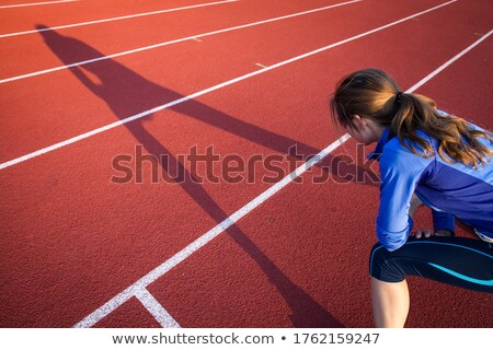 pretty female runner stretching before her run at a track stock photo © lightpoet