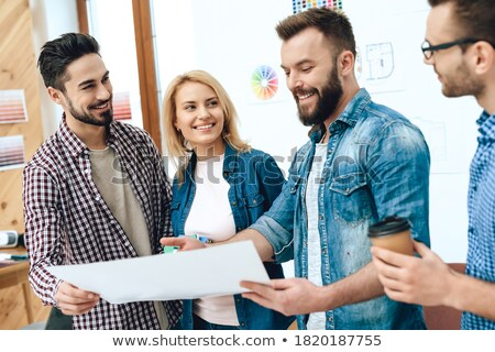 Smiling bearded man standing and working on blueprint in office Stock photo © deandrobot