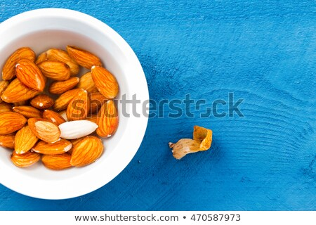 Whole almonds soaked in water over blue table Stock photo © ozgur