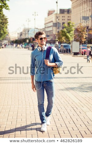 Happy man student with backpack walking outdoors Stock photo © deandrobot