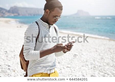 Férfi turista mobiltelefon vízpart nyári szabadság póló Stock fotó © stevanovicigor