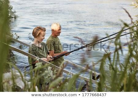 Boy looking at the fishing rod near the river Stock photo © wavebreak_media