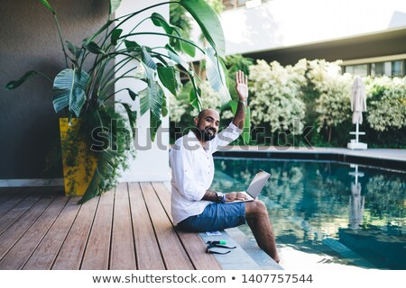 Friends waving from edge of pool Stock photo © IS2