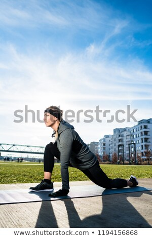 determined young woman stretching her leg while kneeling on a mat stock photo © kzenon