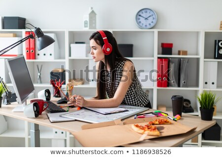 a young girl is standing near a table holding a green marker and looking at the monitor before the stock photo © traimak