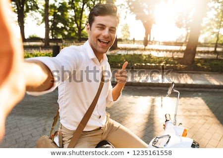 excited young business man walking outdoors on scooter take a selfie by camera stock photo © deandrobot