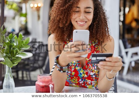 Image of happy woman holding cell phone and credit card in hands Stock photo © deandrobot