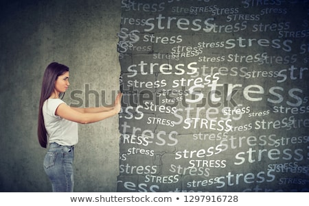 Side view of young woman pushing away block wall with stress Stock photo © ichiosea