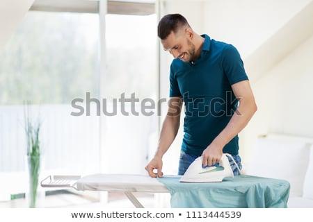 Férfi vasalás póló vasaló otthon házimunka Stock fotó © dolgachov