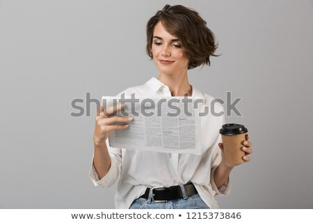 emotional young business woman posing isolated over grey wall background reading newspaper drinking stock photo © deandrobot