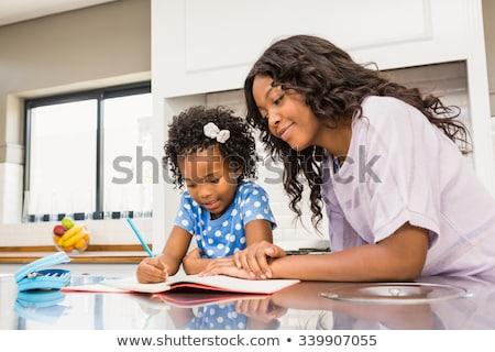 Stock photo: mother help Black girl doing homework at home