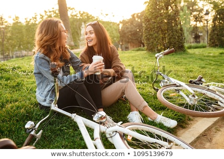 Two young women friends outdoors on bicycles in park. stock photo © deandrobot