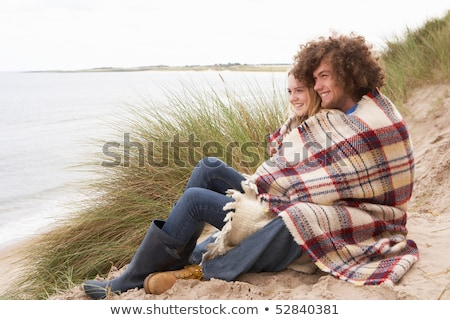 young couple sitting in sand dunes wrapped in blanket stock photo © monkey_business