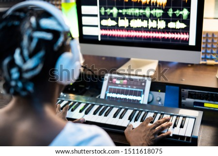 African or mixed-race young man touching keys of piano keyboard by computer Stock photo © pressmaster