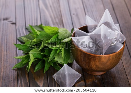 Tea bags on wooden background with fresh melissa, mint. Tea with mint concept Stock photo © galitskaya