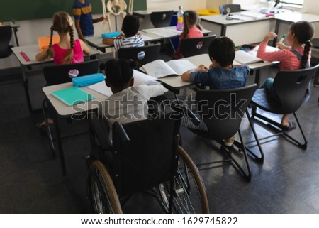 Rear view of disable schoolboy with classmate studying and sitting at desk in classroom of elementar Stock photo © wavebreak_media
