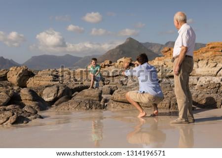 Vue arrière père en fils bras autour téléphone portable Photo stock © wavebreak_media