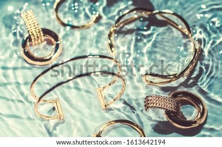 Golden bracelets, earrings, rings, jewelery on blue water backgr Stock photo © Anneleven