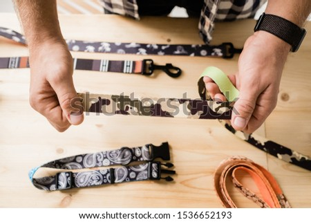 Overview of hands of craftsman holding one of creative pet collar workpieces Stock photo © pressmaster