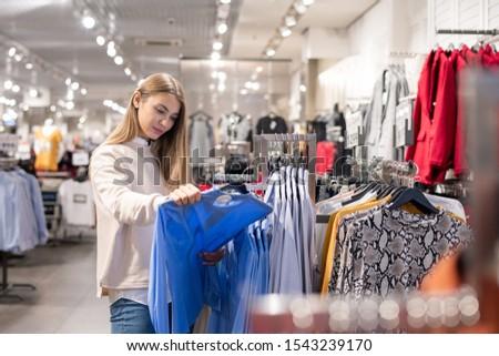Pretty girl in casualwear choosing new shirt in clothing department Stock photo © pressmaster
