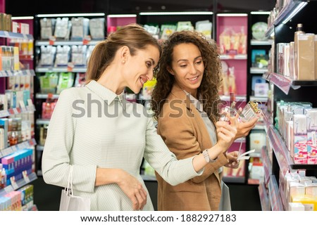 Cheerful young shoppers looking at new departments while standing on escalator Stock photo © pressmaster
