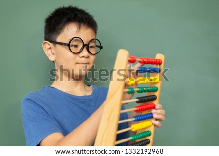 Front view of smart Asian boy learning math with abacus against green chalkboard in a classroom at e Stock photo © wavebreak_media