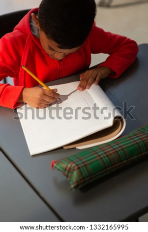 High angle view of cute mixed-race schoolboy writing in a  notebook at desk in classroom at elementa Stock photo © wavebreak_media