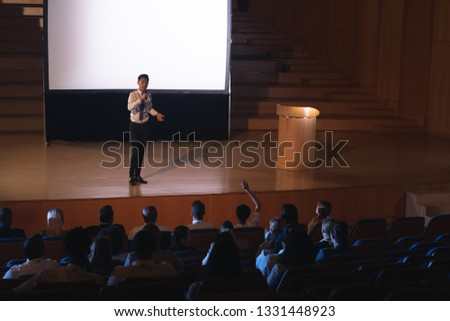 High view of young Asian businessman standing and giving presentation in auditorium while audience r Stock photo © wavebreak_media