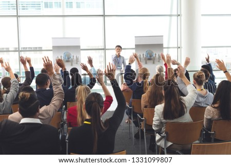 Rear view of diverse business people raising hands at business seminar while they are sitting in fro Stock photo © wavebreak_media