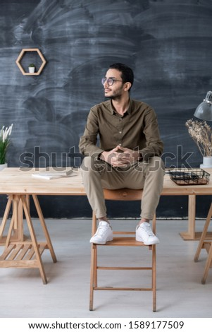 Restful businessman in casualwear sitting on wooden table with his feet on chair Stock photo © pressmaster