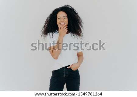 Overjoyed mixed race curly woman being in good mood, holds chin and giggles happily, keeps hand in p Stock photo © vkstudio