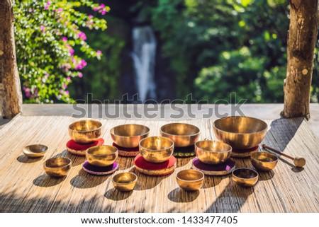 Tibetan singing bowls on a straw mat against a waterfall BANNER, LONG FORMAT Stock photo © galitskaya